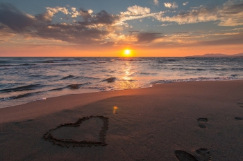heart in sand on beach at sunset